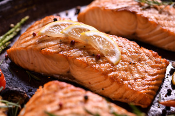 Wall Mural - Grilled salmon fish with various vegetables on pan on the flaming grill