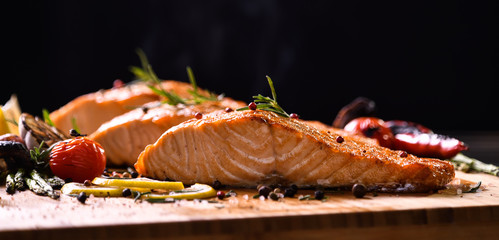Fototapete - Grilled salmon fish and various vegetables on wooden table on black background