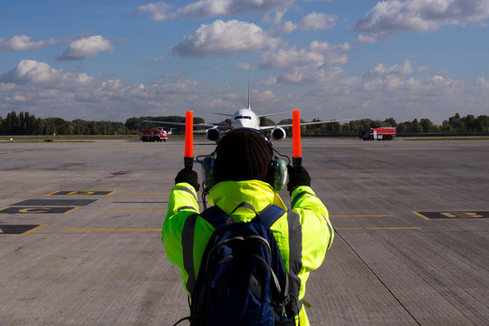 A supervisor helps at the aircraft parking at the airport