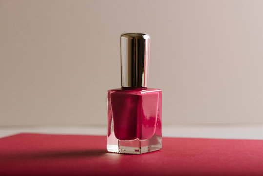 Pink nail polish on pastel color background