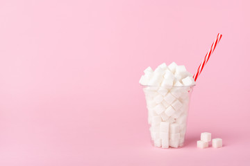 Shake Glass full of sugar cubes on pink background Unhealthy food concept Wall mural