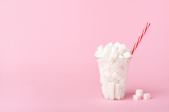 Shake Glass full of sugar cubes on pink background Unhealthy food concept