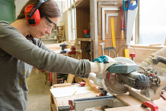 Young woman cutting a wooden plank with a circular saw in a workshop