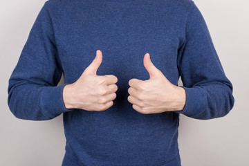 Cropped close up photo studio image of confident chief ceo student  coach expressing leadership using hands giving two fingers up wearing formal blue sweater isolated grey background