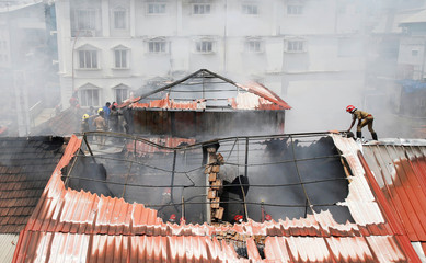 A firefighter walks on the rooftop as others try to douse a fire that broke out at a wholesale market in Kochi