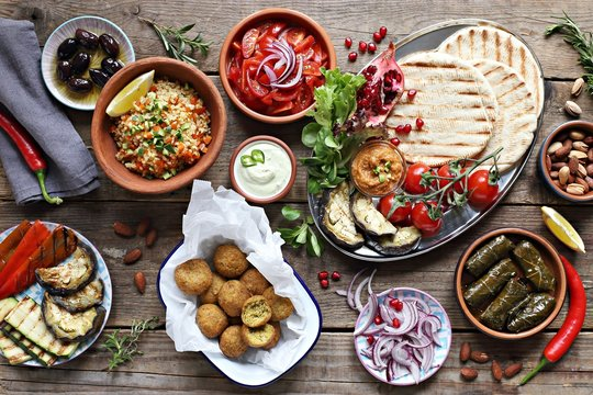Middle eastern, arabic or mediterranean appetizers table concept with falafel, pita flatbread, bulgur and tomato salads, grilled vegetables, stuffed grape leaves,olives and nuts.