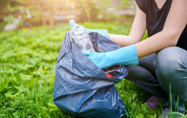 Picture of woman in rubber gloves picking up dirty plastic bottle on lawn