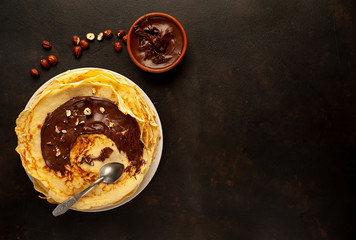 Pancakes with chocolate paste and hazelnuts, on a white plate on a background of concrete, slate with copy space for your text