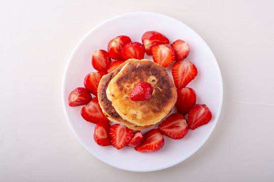 Cottage cheese pancakes with sliced strawberries on white plate isolated