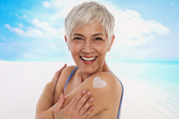 Woman applying Sunscreen spray / sunblock lotion outdoors outdoor on the beach