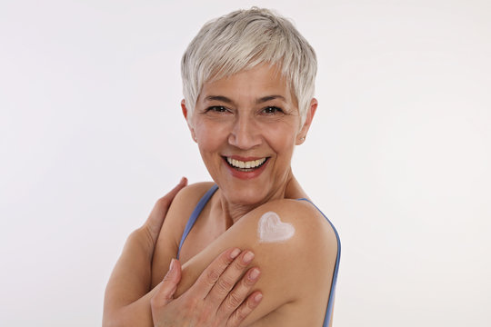 Sun protection, Mature Skin care . Woman applying moisturizing cream, hugging herself .