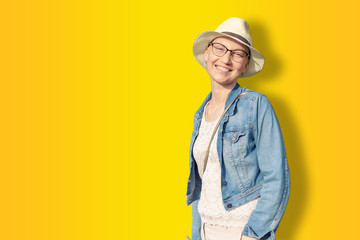 Happy young caucasian bald woman in hat and casual clothes enjoying life after surviving breast cancer. Portrait of beautiful hairless girl smiling isolated on golden yellow background Wall mural