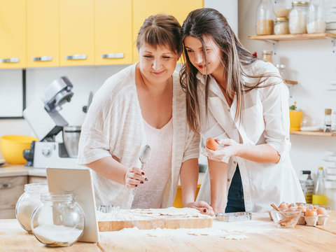 Women making pastries. Mother daughter looking at tablet. Recipe cooking class course online. Home baking hobby fun.