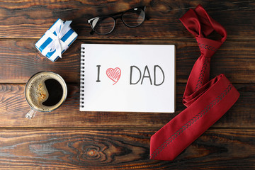 Notebook with inscription I love DAD, cup of coffee, glasses, gift box and tie on wooden background, space for text and top view
