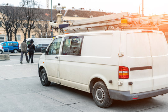 White repair and service van with ladder and orange light bar on roof at city street. Assistance or installation team vehicle