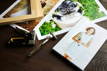 Photo canvas prints. Tools for wrapping.  Photographs, stretcher bars, staple gun and canvas pliers on brown wooden table