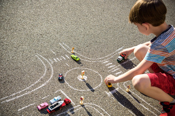 Funny kid boy having fun with picture drawing traffic car with chalks. Creative leisure for children outdoors in summer. Difficult traffic rules concept