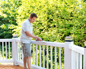 Mature man scraping old paint from outdoor deck