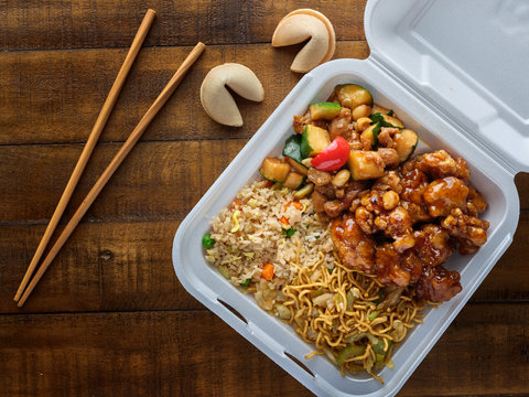 chinese take out with fried rice and general tsos chicken on table top