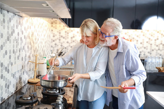caucasian elderly wife making food in the kitchen with her caucasian elderly husband during his retirement life on table in happy holiday
