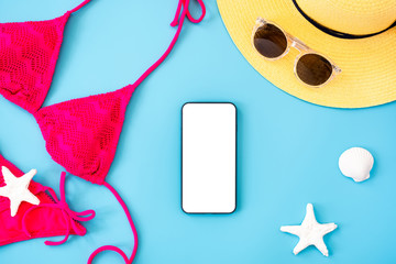 Wall Mural - summer blue banner with yellow hat ,pink bikini,mobile ,sunglasses and seashell on blue background top view mock up screen
