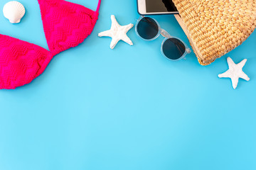 Wall Mural - summer blue banner with pink bikini, wicker bag,sunglasses and seashell on blue background top view.