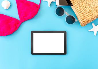 Wall Mural - summer blue banner with yellow wicker bag ,pink bikini,tablet ,sunglasses and seashell on blue background top view mock up screen