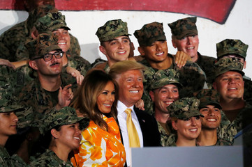 U.S. President Donald Trump and first lady Melania Trump take photos with military personnel aboard the USS Wasp as they participate in a Memorial Day Address in Yokosuka