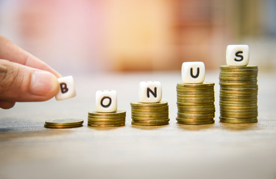 Yearly Bonus concept / hand holding words of bonus on stack coins staircase