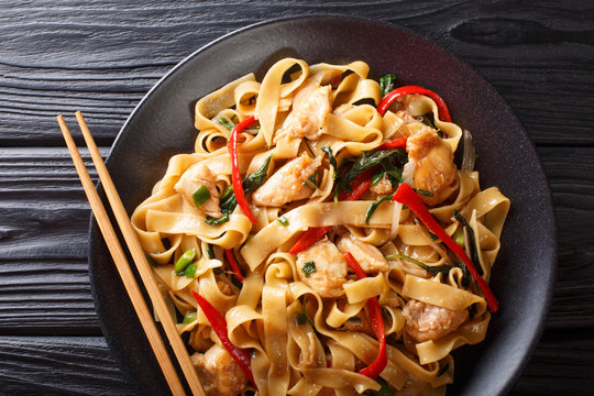 Drunken noodles pad kee mao with chicken, basil, chili pepper and sauce close-up on a plate. horizontal top view