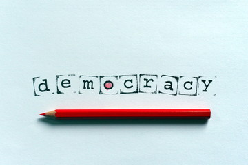 The word democracy written with stamps and ink on white paper, and a red wooden pencil, concept image