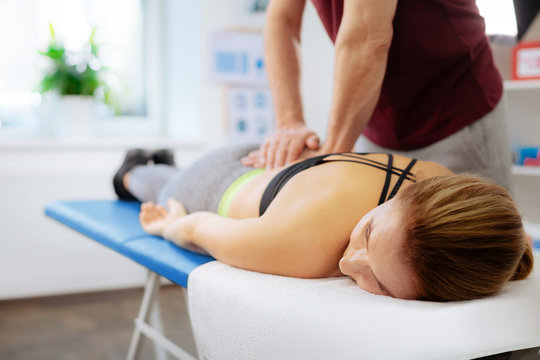 Pleasant relaxed woman receiving a back massage