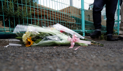 Flowers are offered at the site where a stabbing occured in Kawasaki city