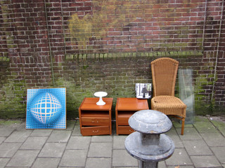 collection of furniture: garbage placed against a wall on the street