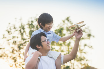 Asian father and son playing wooden airplane together