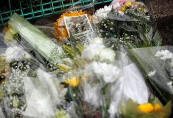 Flowers and a picture are offered to mourn victims at the site where a stabbing occured in Kawasaki