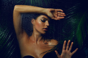 A beautiful, young, tanned girl with wet hair and wet skin is standing in the jungle in the rain.