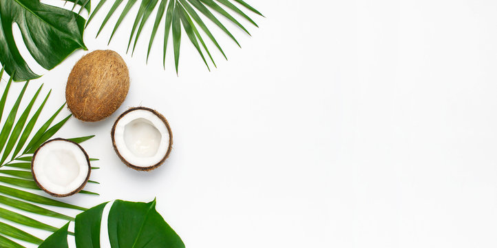 Tropical leaves and fresh coconut on light gray background. Flat lay, top view, copy space. Summer background, nature. Healthy cooking. Creative healthy food concept, half of coconut