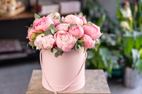 Pink peonies on the old grey table. Beautiful peony flower for catalog or online store. Floral shop concept . Beautiful fresh cut bouquet. Flowers delivery