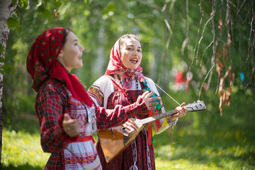 Two young woman in traditional russian clothes singing in the forest. One of them playing balalaika Wall mural