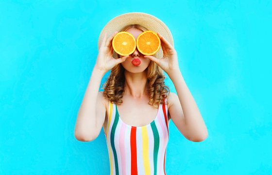 Summer portrait woman holding in her hands two slices of orange fruit hiding her eyes in straw hat on colorful blue background