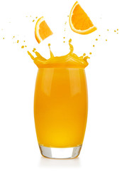 Wall Mural - orange slices falling into a splashing juice glass isolated on white