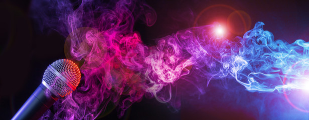 microphone and colorful smoke swirls on black background