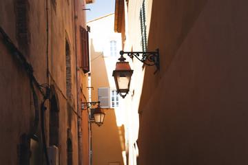 Antique lantern on a wall on a narrow european street, details of European architecture