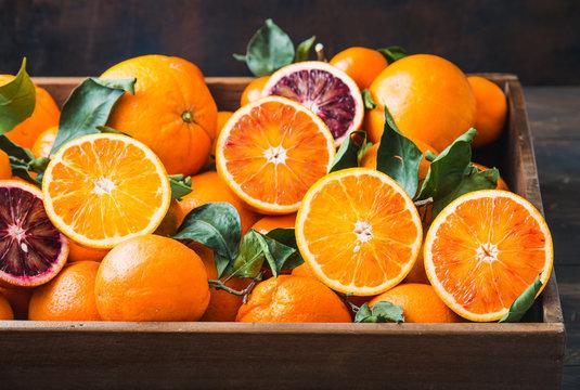Oranges citrus fruits close up dark background in wooden box..