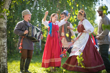 People in traditional Russian clothes are dancing in the woods - one of them plays the accordion and singing Wall mural