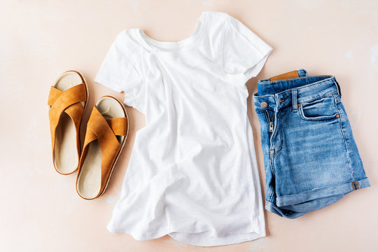 Woman's casual summer vacation outfits with white t-shirts, denim shorts, trendy leather sandals, with crisscross details on pink pastel background.