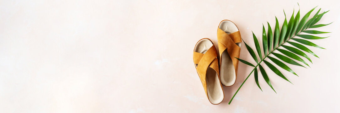 Woman's casual trendy leather sandals with crisscross details for summer vacation outfits on pink pastel background with palm leaf. Long wide banner.