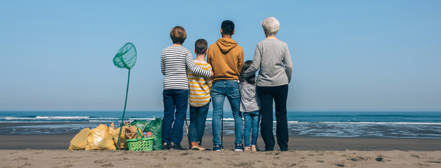 Group of volunteers backwards watching the sea after cleaning the beach