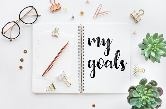 My goal concepts with text on notepad with accessories on white desk table background
